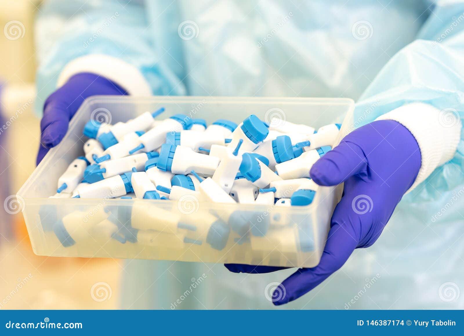 Escarificadores para el an?lisis de la sangre en las manos de un ayudante de laboratorio