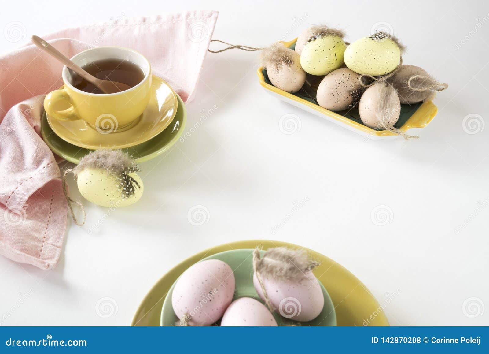 Escena de la mañana de Pascua en colores en colores pastel, con té y rosa y huevos amarillos