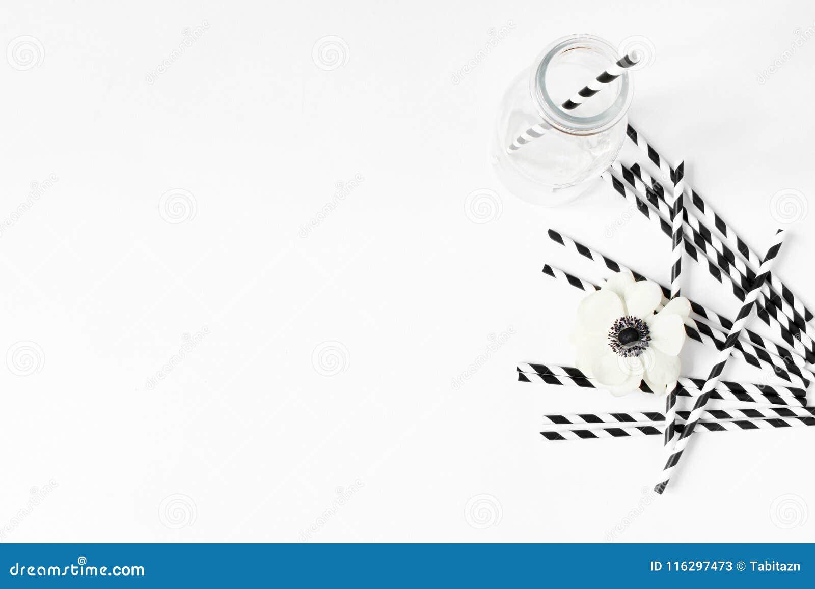 Escena de la mesa del desayuno o de la fiesta de cumpleaños Composición con el tarro vacío del vidrio de leche, paja de papel de