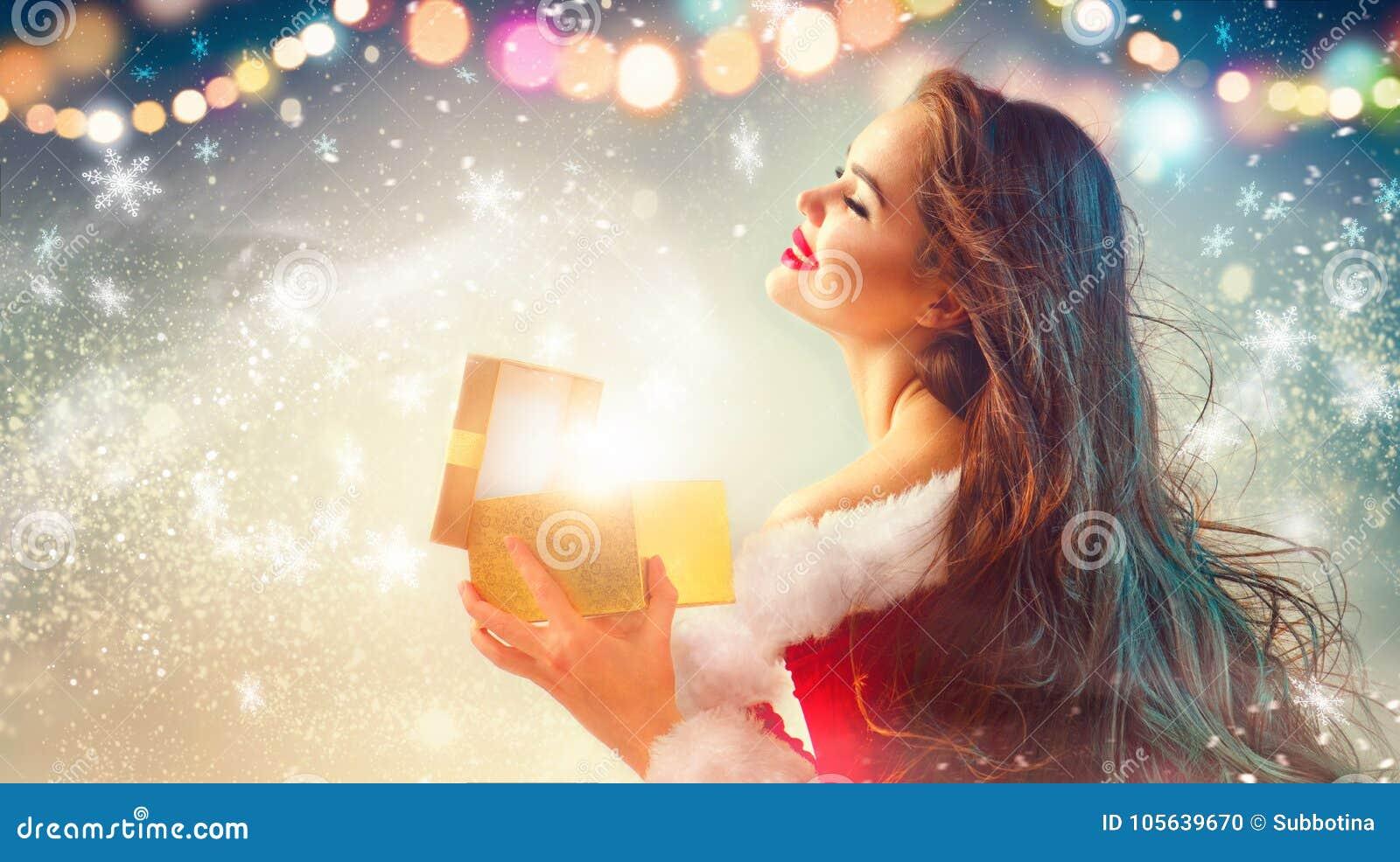 Escena de la Navidad Mujer joven morena de la belleza en caja de regalo de la abertura del traje del partido