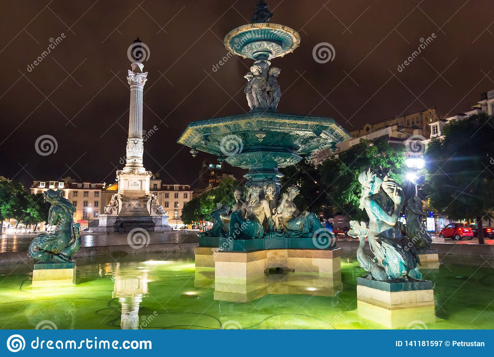 Escena de la noche del cuadrado de Rossio, Lisboa, Portugal con uno de sus fuentes decorativas y de la columna de Pedro IV