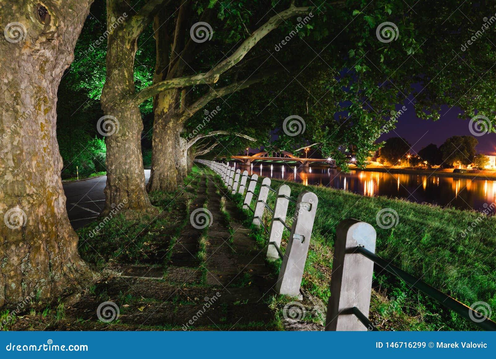 Escena de la noche del paseo lateral abandonado cerca del río