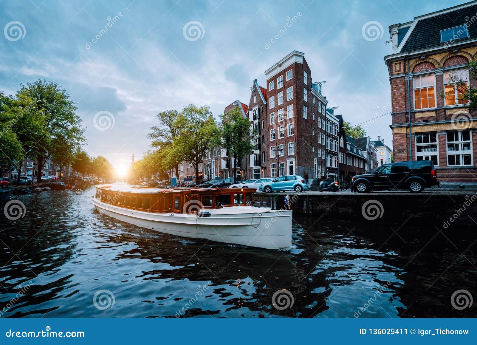 Escena de la puesta del sol en la ciudad de Amsterdam Gran barco turístico en el canal holandés famoso que flota casas inclinadas