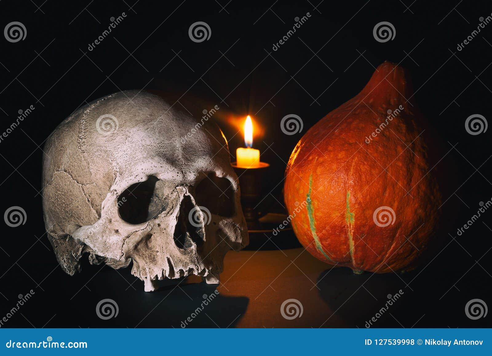 Escena de Víspera de Todos los Santos Cráneo humano cerca de la calabaza de Halloween con la vela ardiente en fondo del negro osc