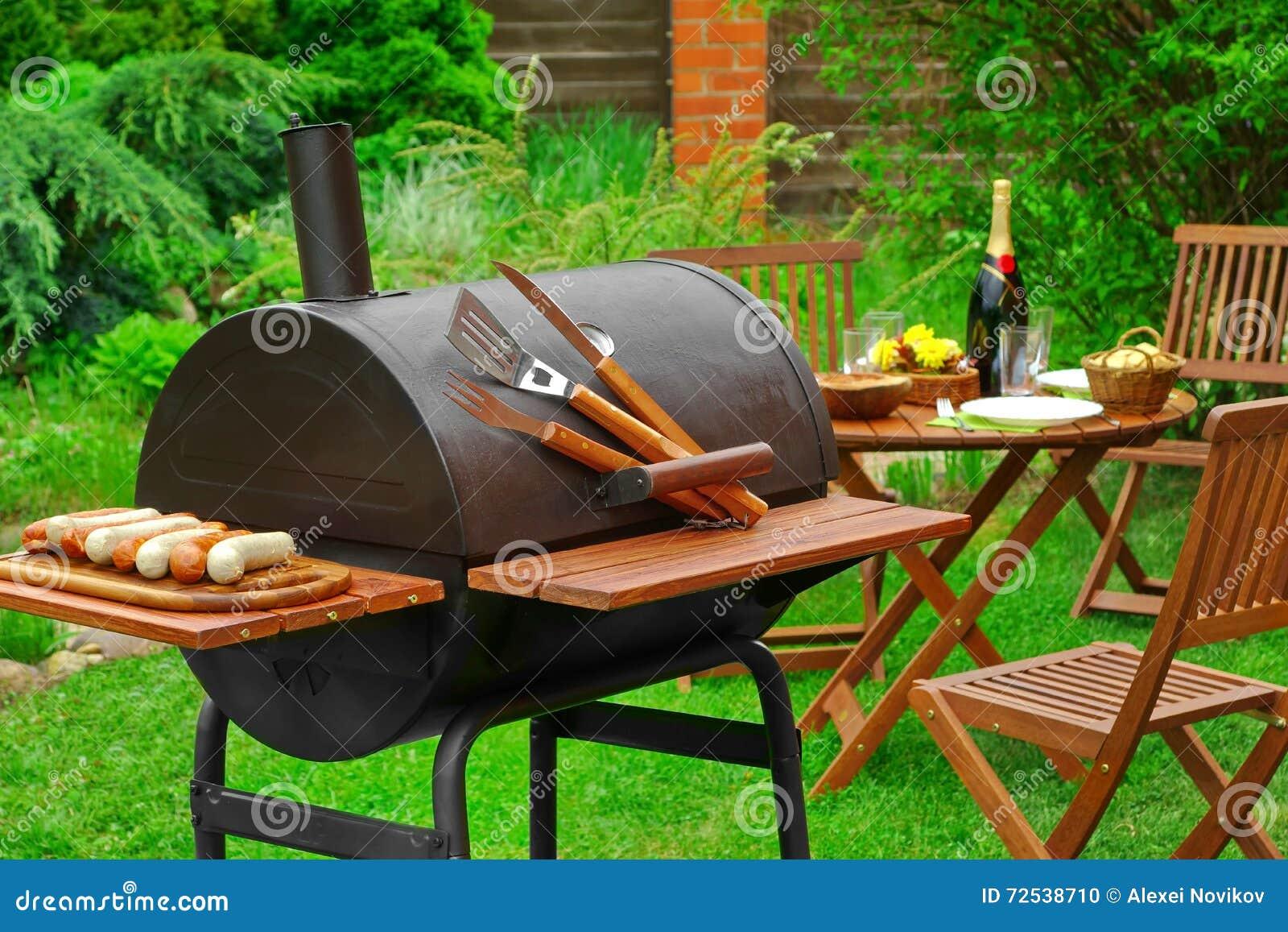 Escena del Bbq del fin de semana del verano con la parrilla del carbón de leña en el patio trasero
