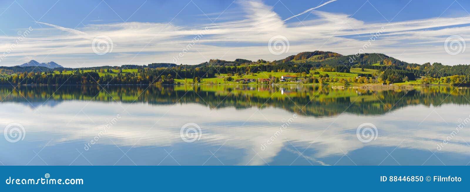 Escena del panorama en Baviera con las montañas que duplican en el lago