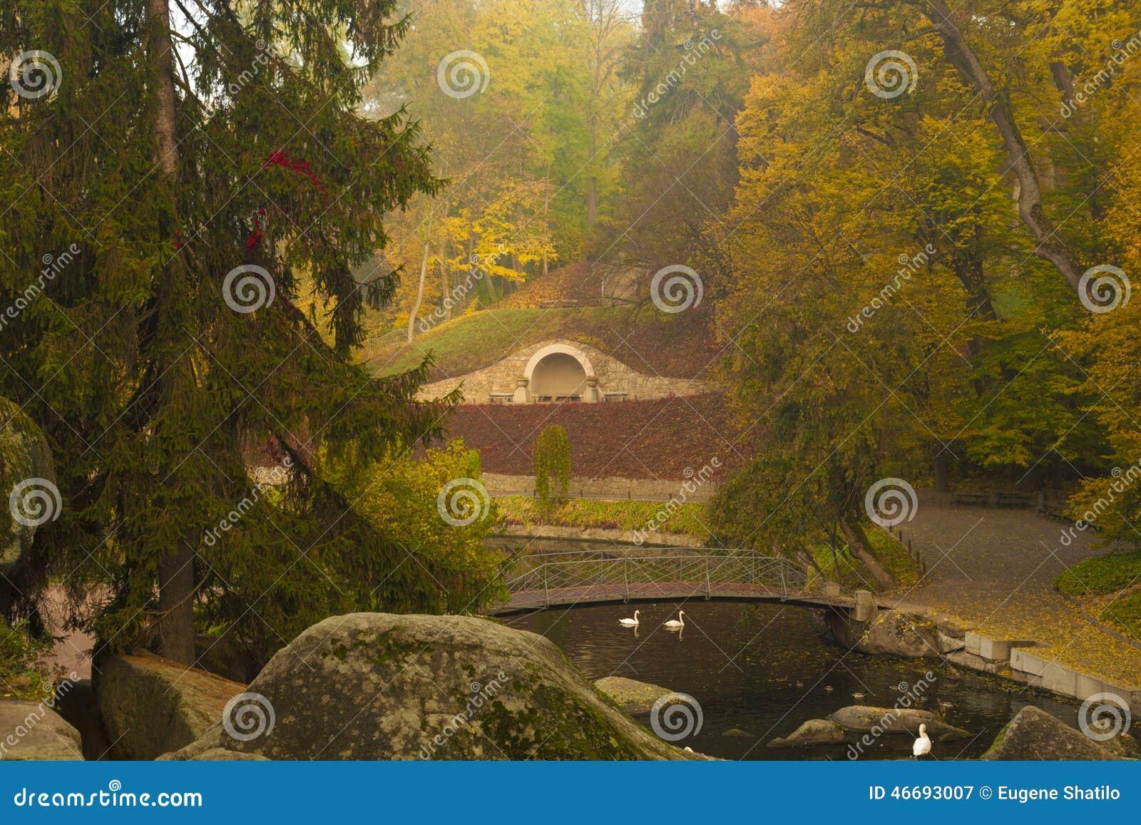 Escena del parque del otoño con el río