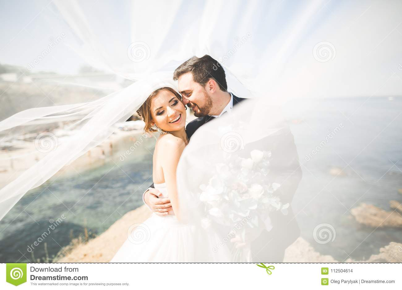 Escena feliz y romántica apenas de la pareja joven casada de la boda que presenta en la playa hermosa