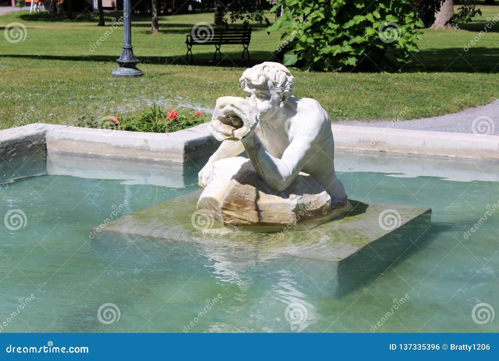 Escena pacífica con la fuente y la estatua de mármol del 'escupitajo y de la polaina 'que llevan en el parque del congreso, Sarat