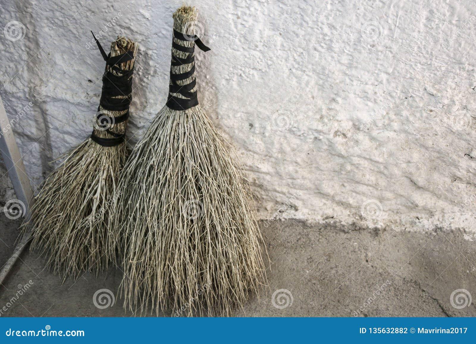 Escobas hechas a mano naturales cerca de la pared llana blanca