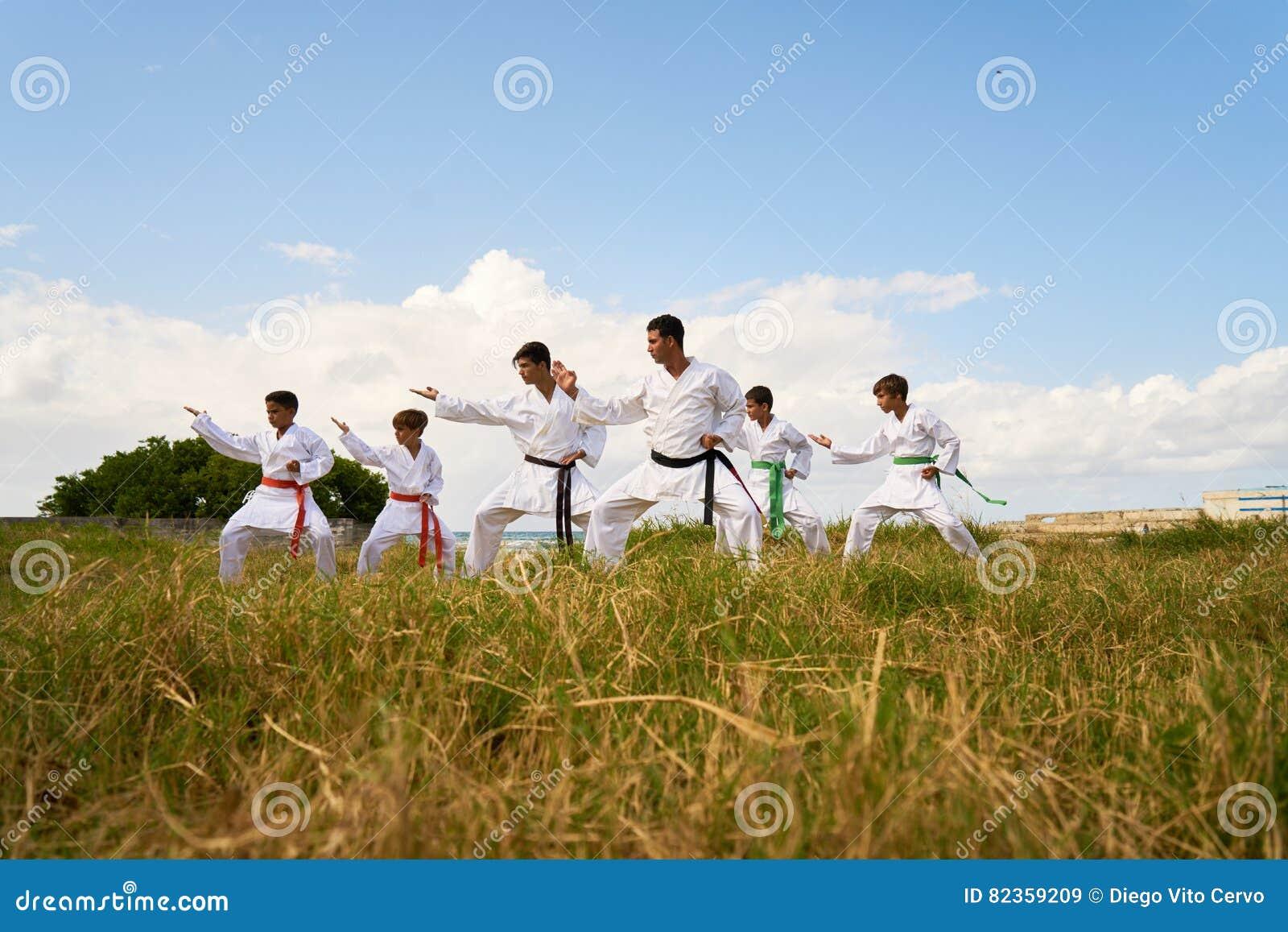 Escola do karaté com aquecer-se dos instrutores e dos meninos