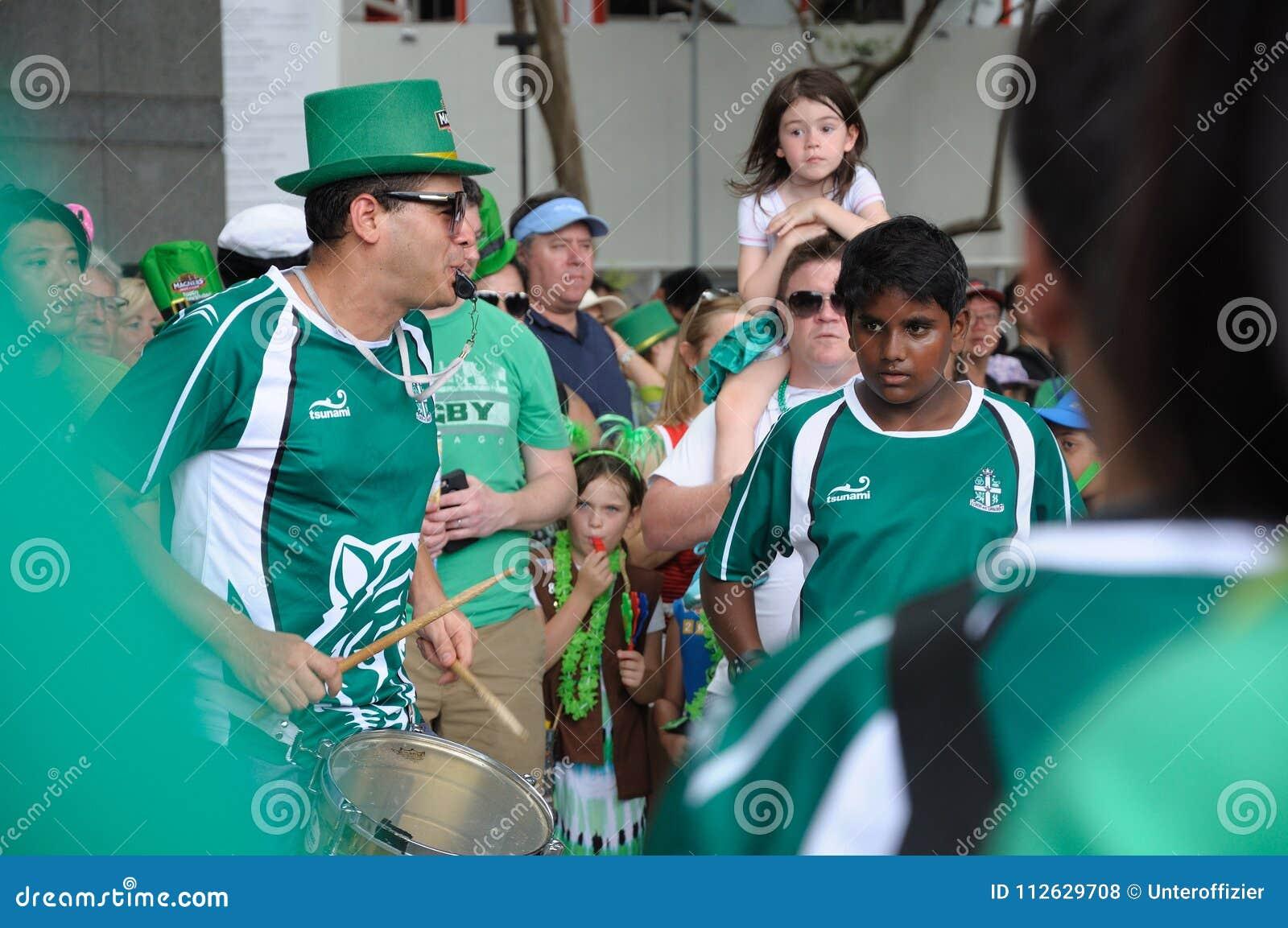 Escola internacional Samba Drummers de SJI no dia do ` s de St Patrick em Singapura