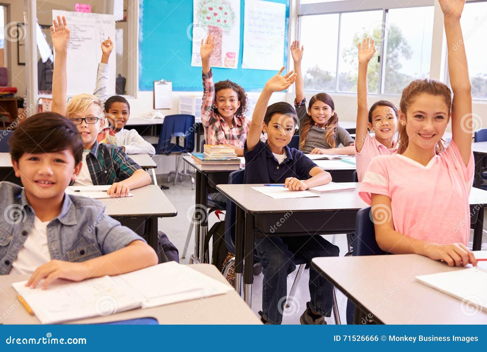 A escola primária caçoa em uma sala de aula que levanta suas mãos