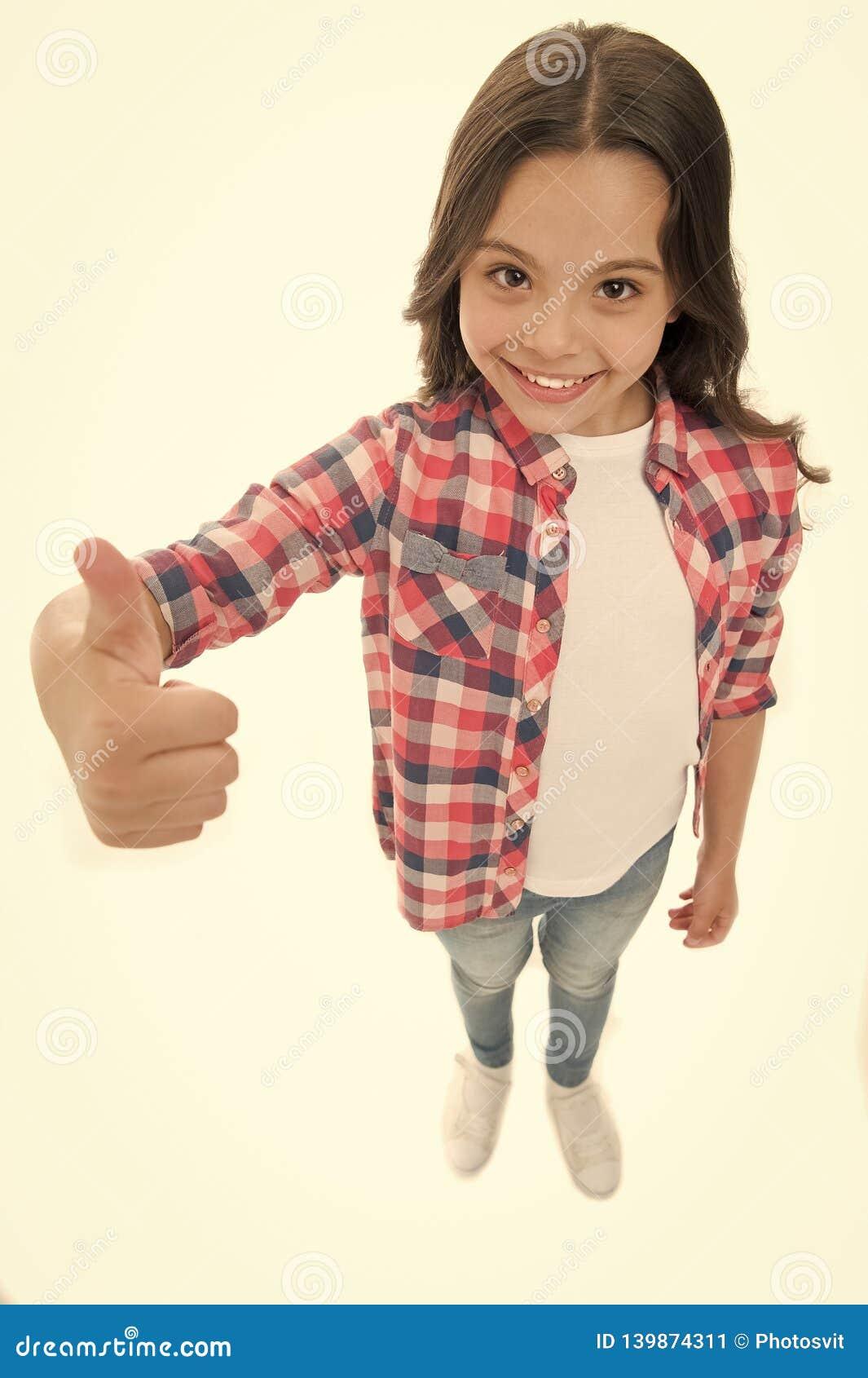 Escolha agradável Recomende altamente A menina da criança mostra o polegar acima do gesto, fundo branco isolado Criança de sorris