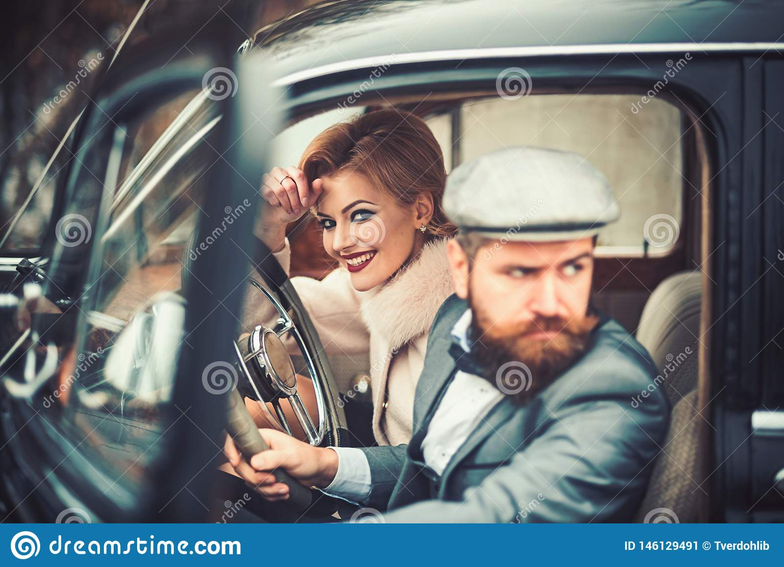 Escort of girl by security. escort concept with bearded driver and luxury girl in retro car.
