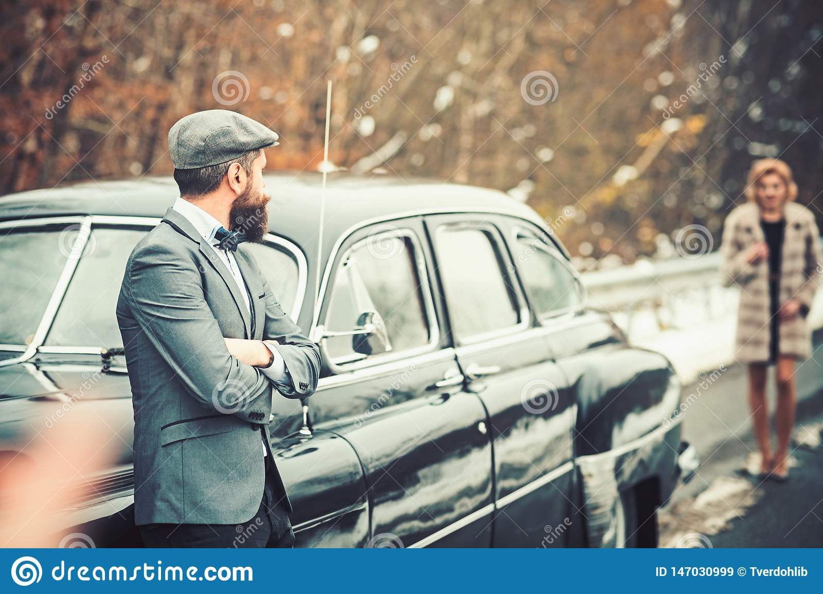 Escort of girl by security. Retro collection car and auto repair by mechanic driver. Bearded man and woman in fur