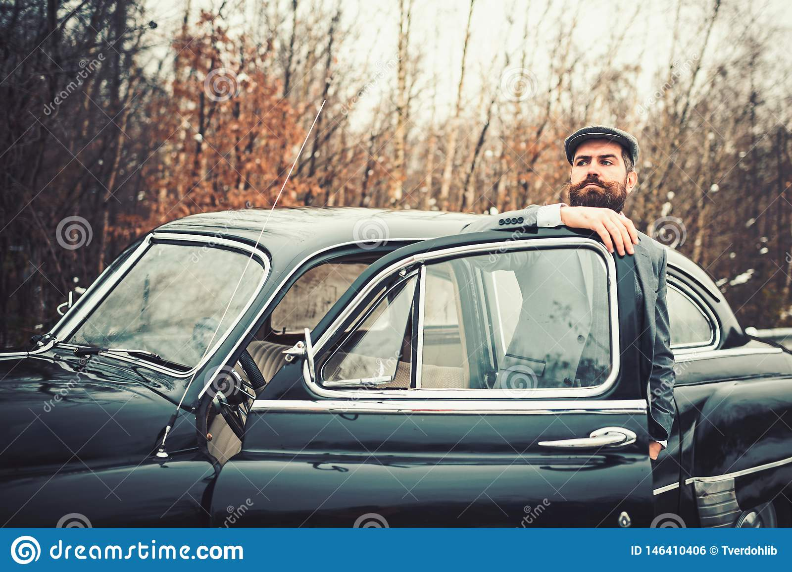 Escort man or security guard. Bearded man in car. Call boy in vintage auto. Retro collection car and auto repair by