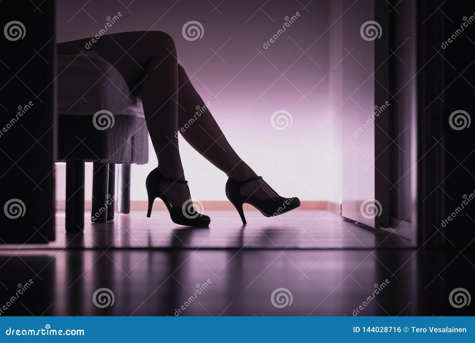 Escorte, prostituee of suiker die babe op bed met lange benen en sexy hoge hielen liggen Prostitutie, het geslachtswerk of suiker