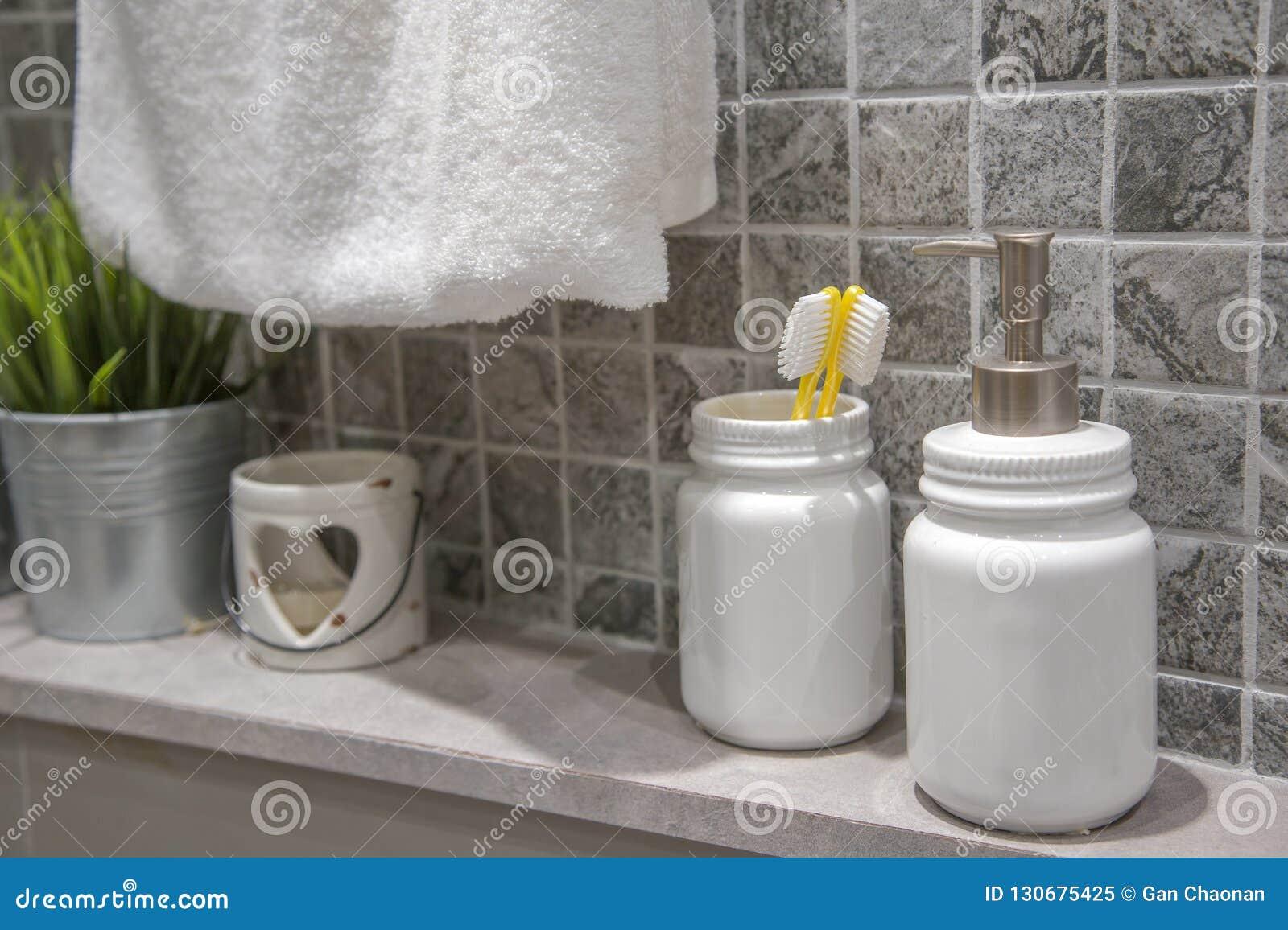 A escova de dentes amarela está no frasco branco no banheiro,
