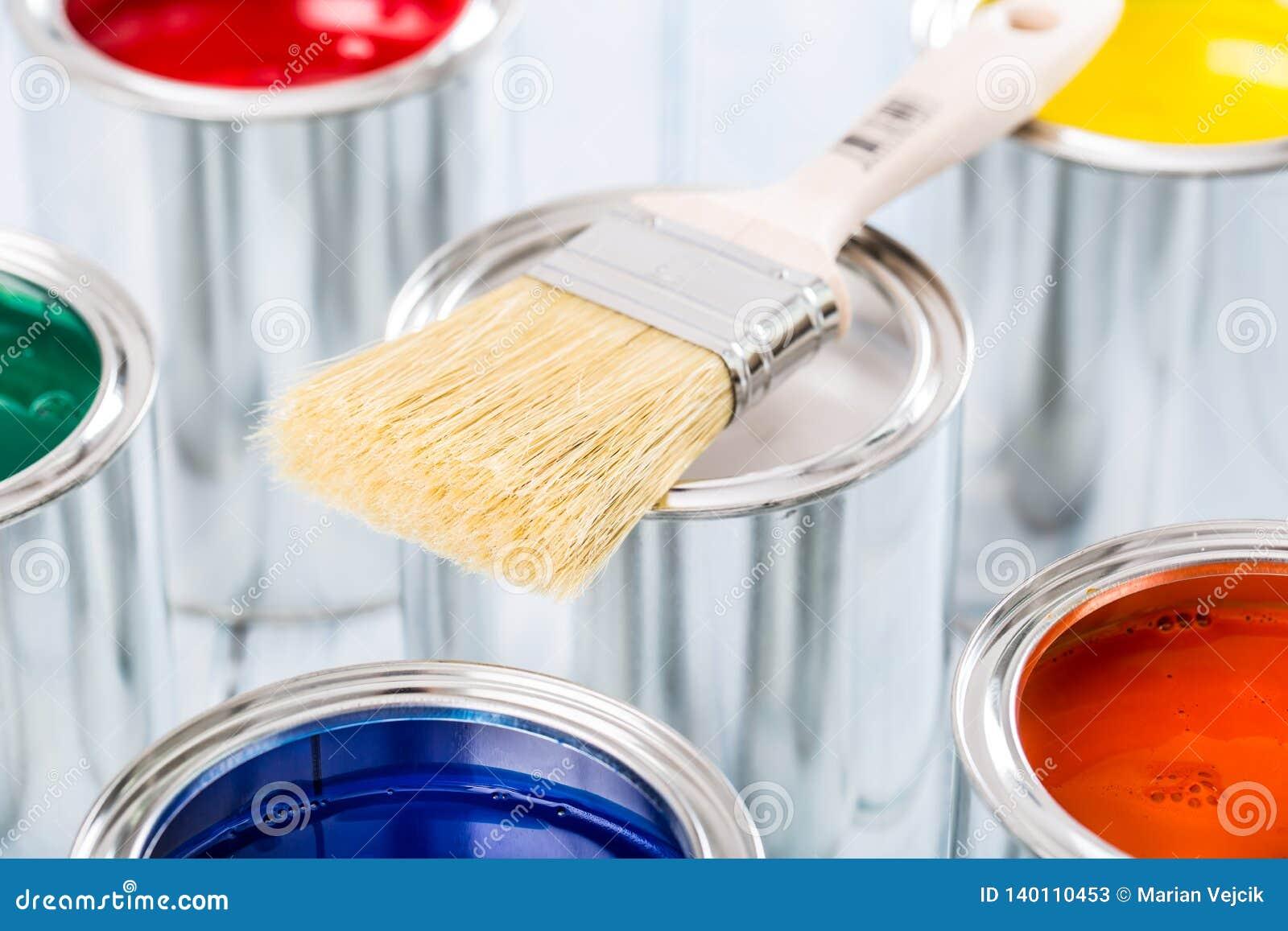 Escova do close-up que encontra-se em latas coloridos da pintura