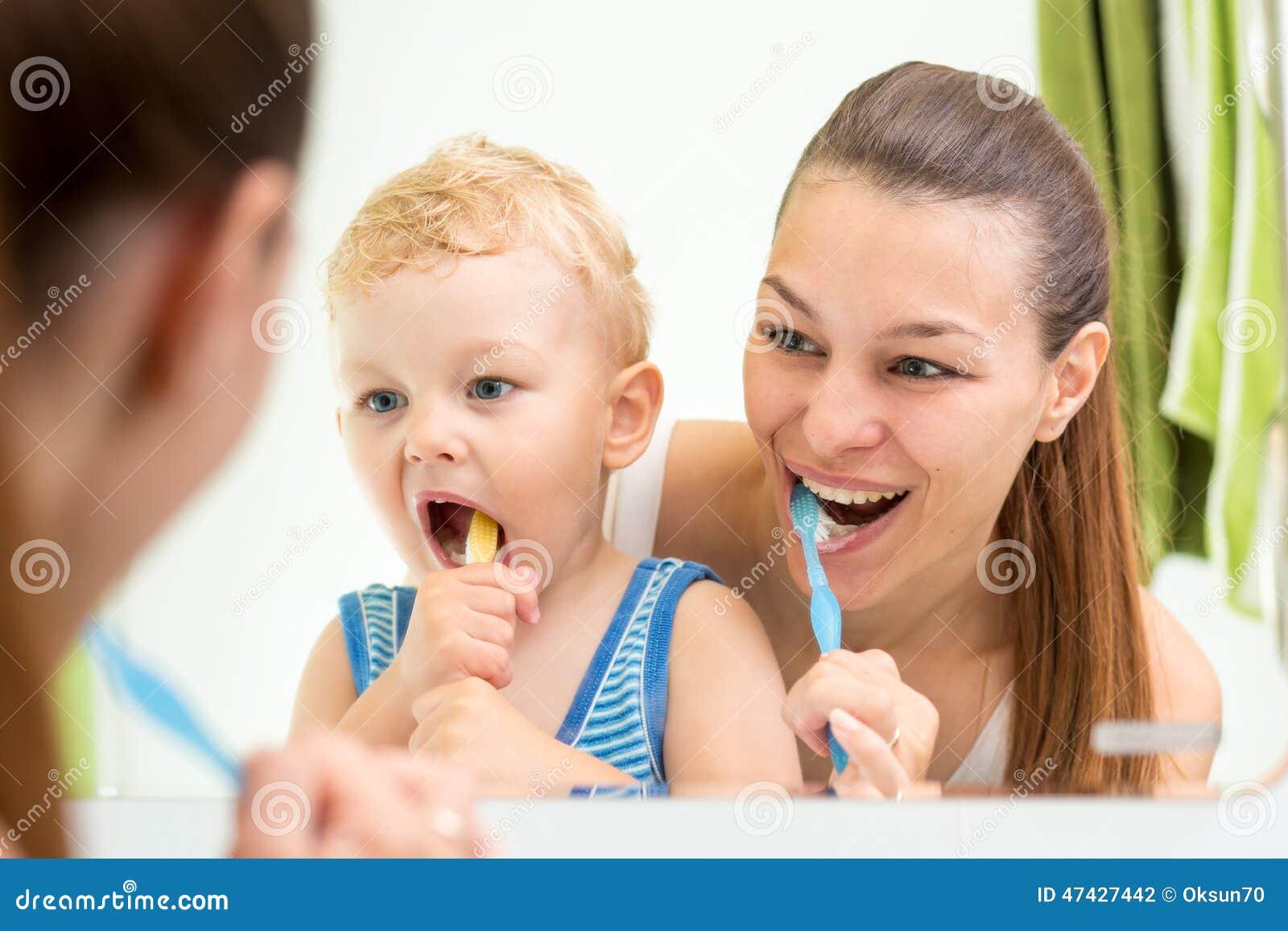 Escovadela de dentes da criança do ensino da mãe