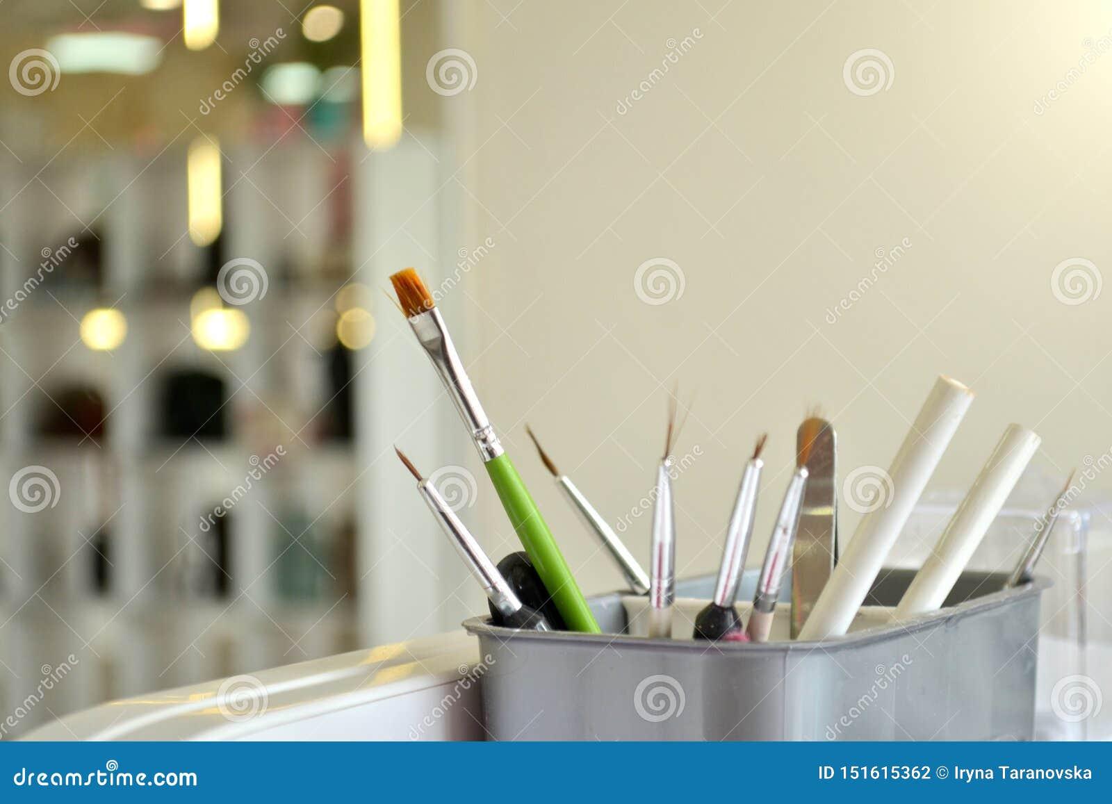 Escovas e ferramentas para o tratamento de mãos e o nailart no vidro branco no salão de beleza no fundo de um espelho e de umas a