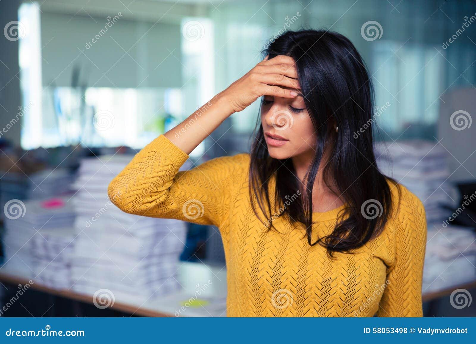 Escritório de Having Headache In da mulher de negócios
