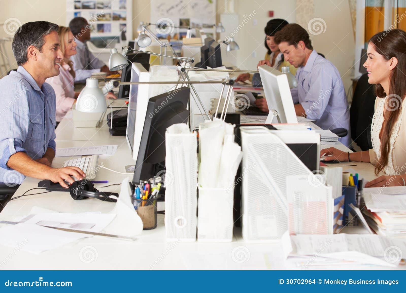 Escritório ocupado de Team Working At Desks In
