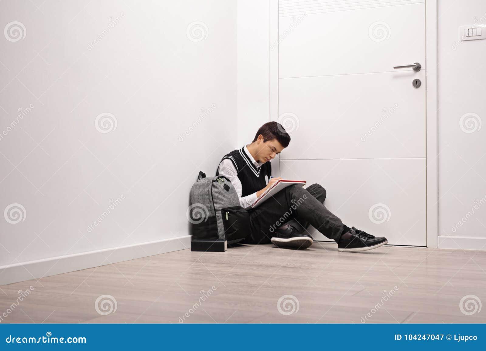 Escrita adolescente triste do estudante em um caderno dentro