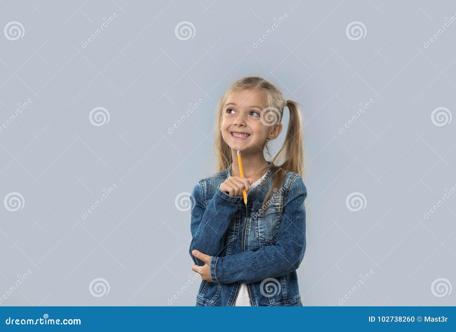 Escrita bonita do lápis da posse da menina que pensa a vista de sorriso feliz para copiar o espaço isolado