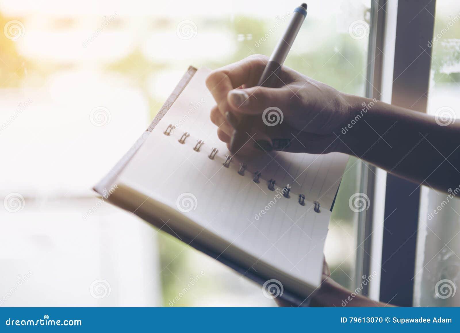 Escrita da mulher no caderno vazio na cama na manhã