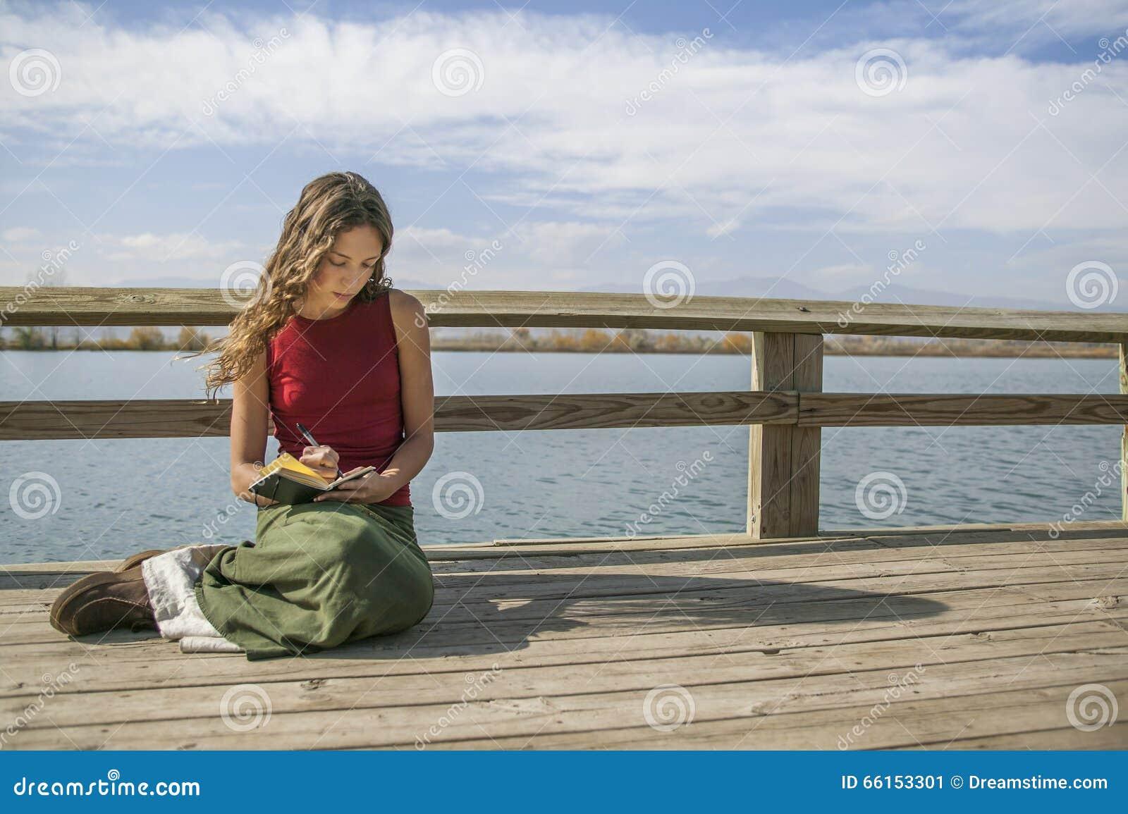 Escrita de cabelos compridos bonita da mulher no jornal perto do lago rural