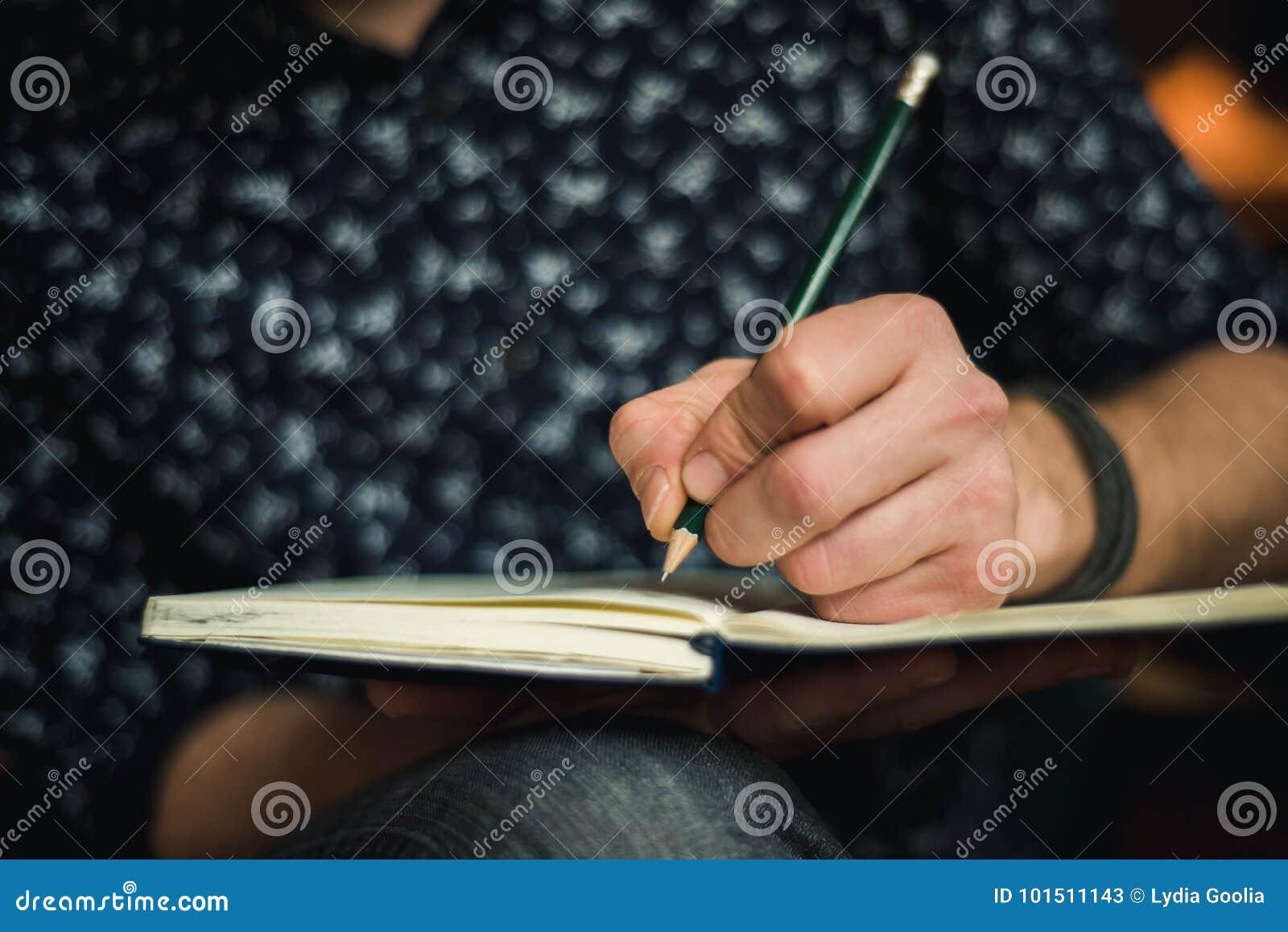 Escrita do homem no jornal com um lápis