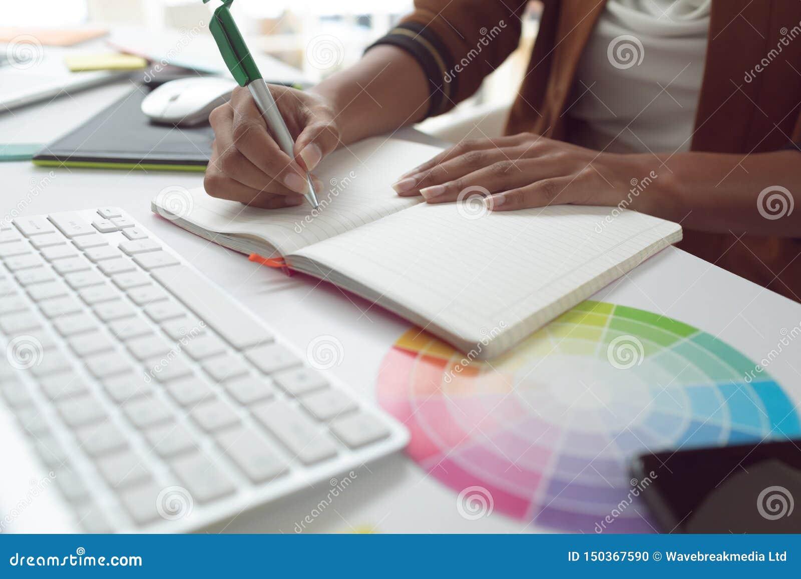 Escrita fêmea do designer gráfico no diário na mesa em um escritório moderno