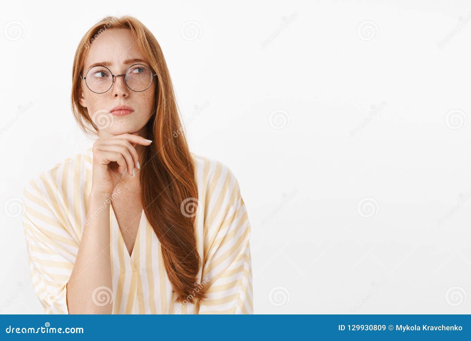 Escritor de sexo femenino creativo pensativo y concentrado en cuestión con el pelo y las pecas rojos en vidrios y amarillo de mod
