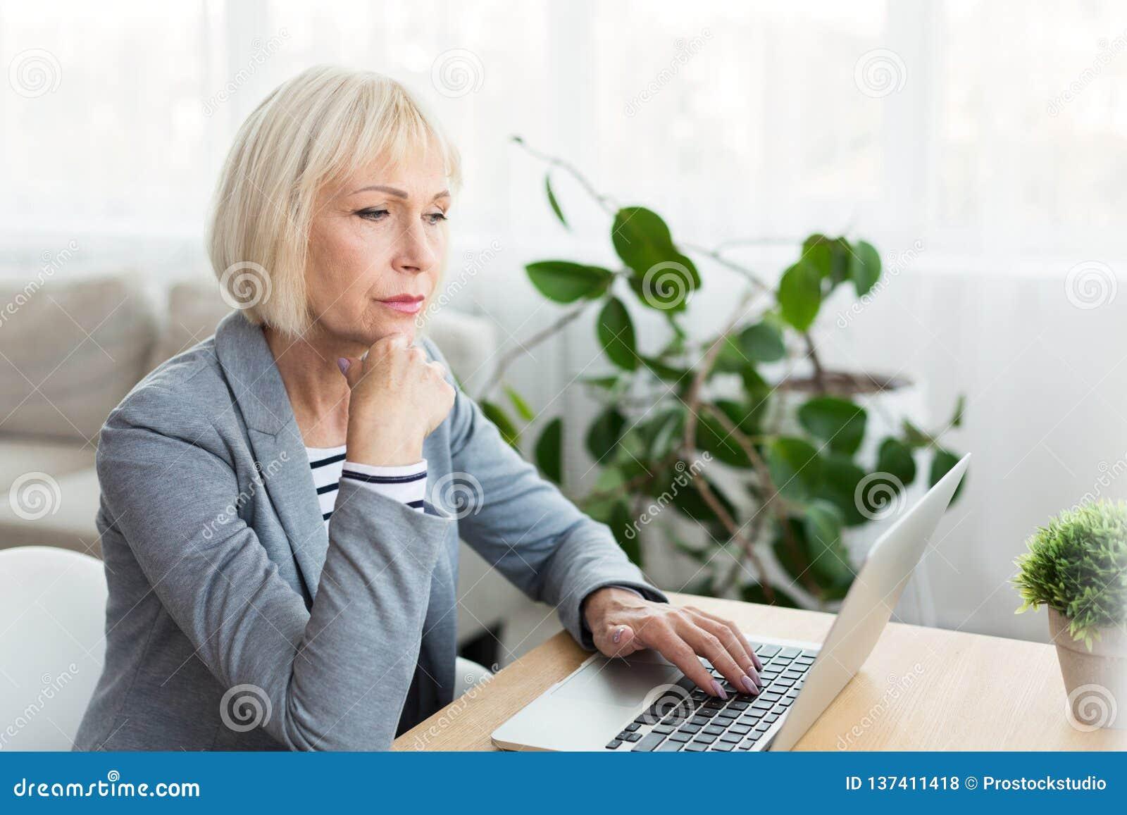 Escritor mayor de la mujer en el funcionamiento blanco en el nuevo artículo