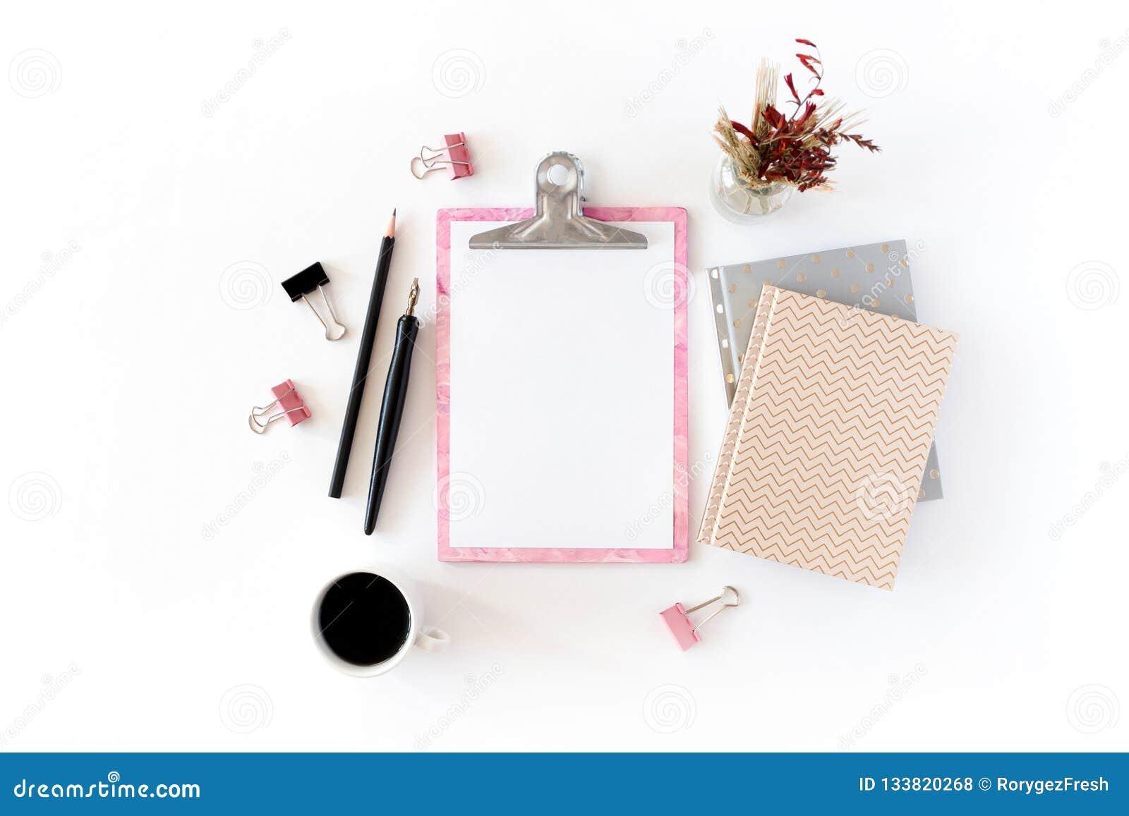 Escritorio de Ministerio del Interior con el tablero rosado, libretas, ramo de flores secas, pluma caligráfica, lápiz, clips de p