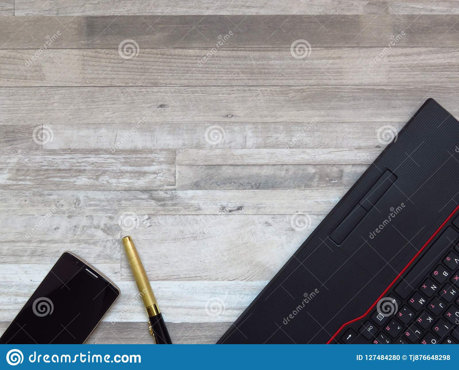 Escritorio de oficina con el ordenador portátil negro, teléfono móvil del color de oro, pluma lujosa de oro en el fondo de madera