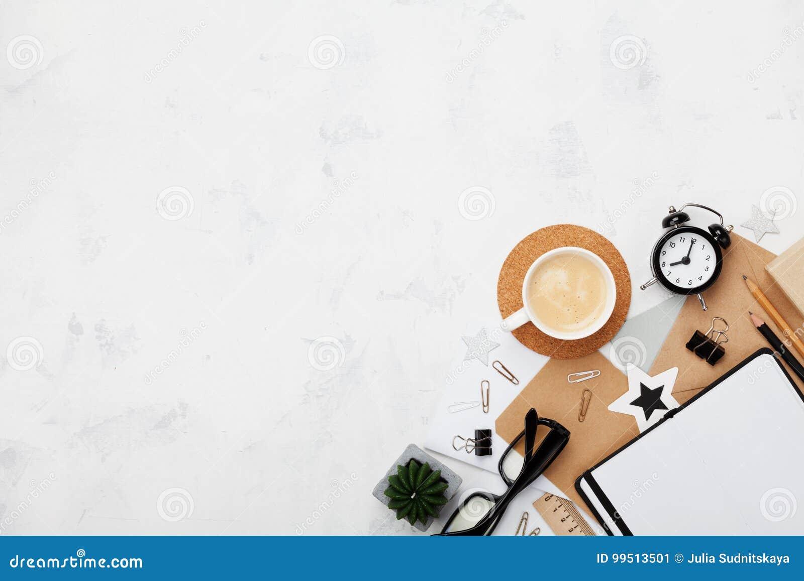 Escritorio de trabajo del blogger elegante con café, material de oficina, el despertador y el cuaderno limpio en la opinión de so
