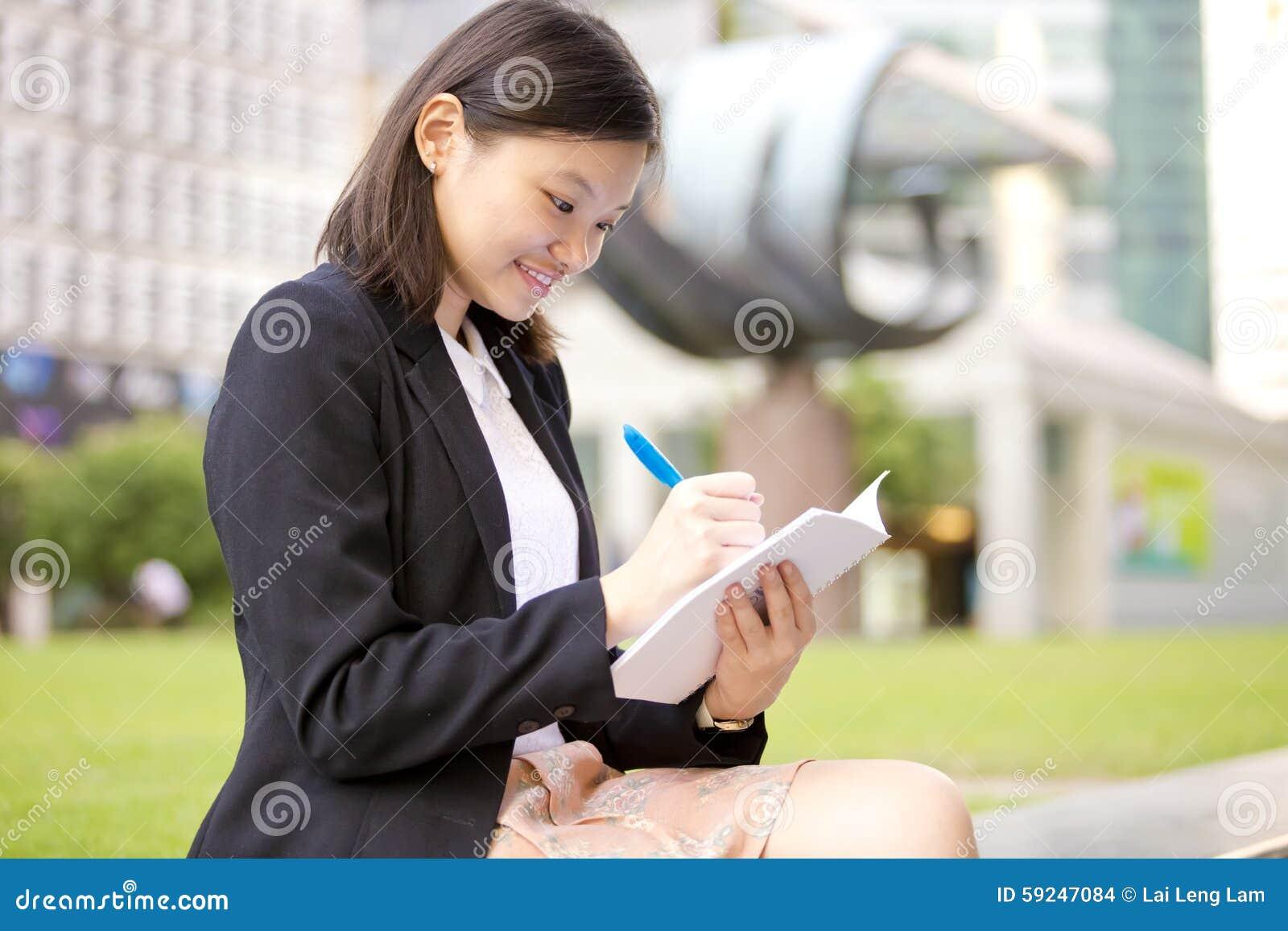 Escritura ejecutiva femenina asiática joven en la libreta