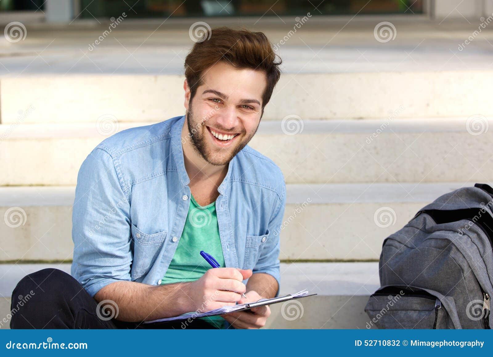 Escritura feliz del estudiante universitario en la libreta afuera