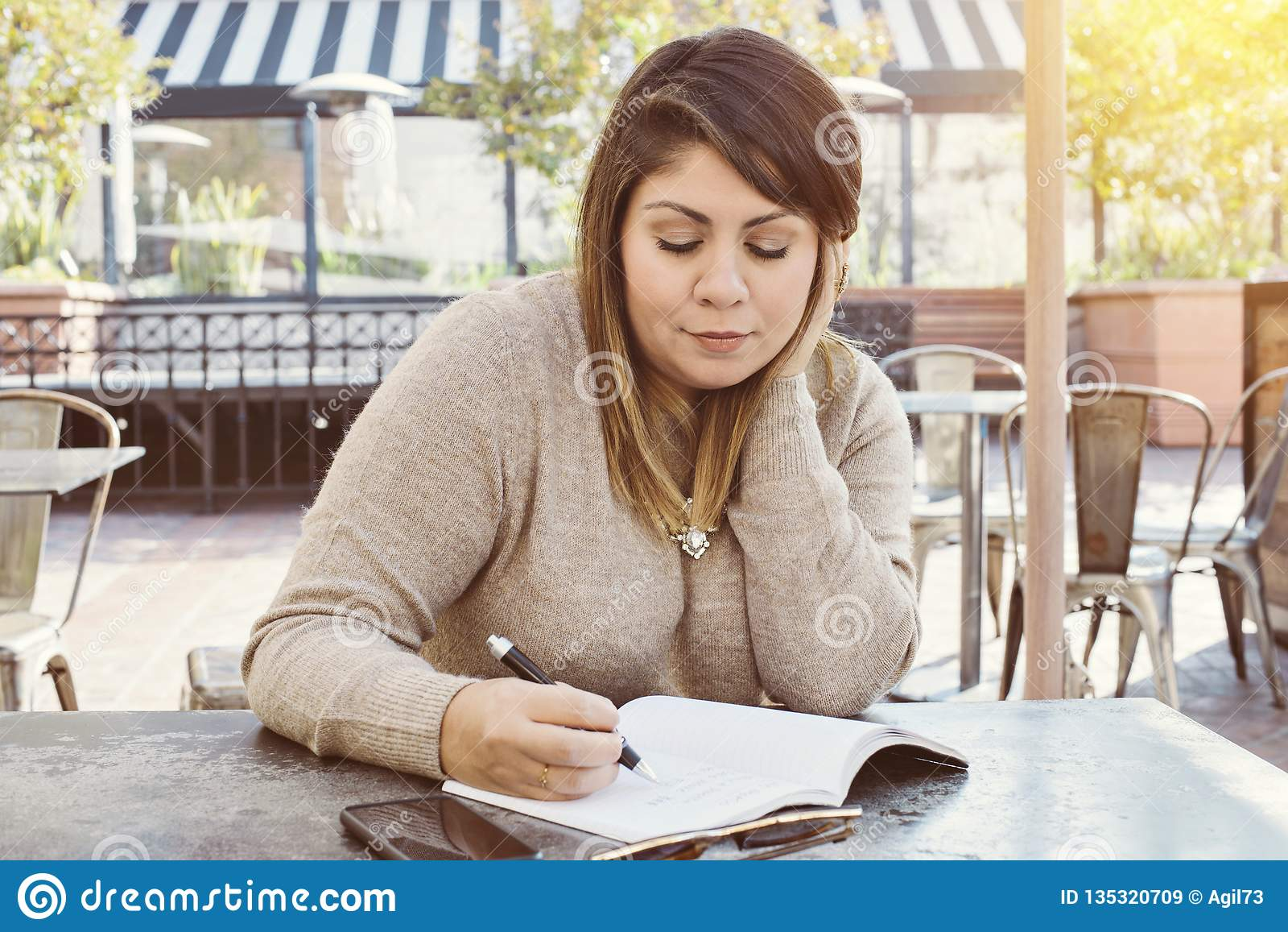 Escritura femenina hispánica en su diario en un café al aire libre