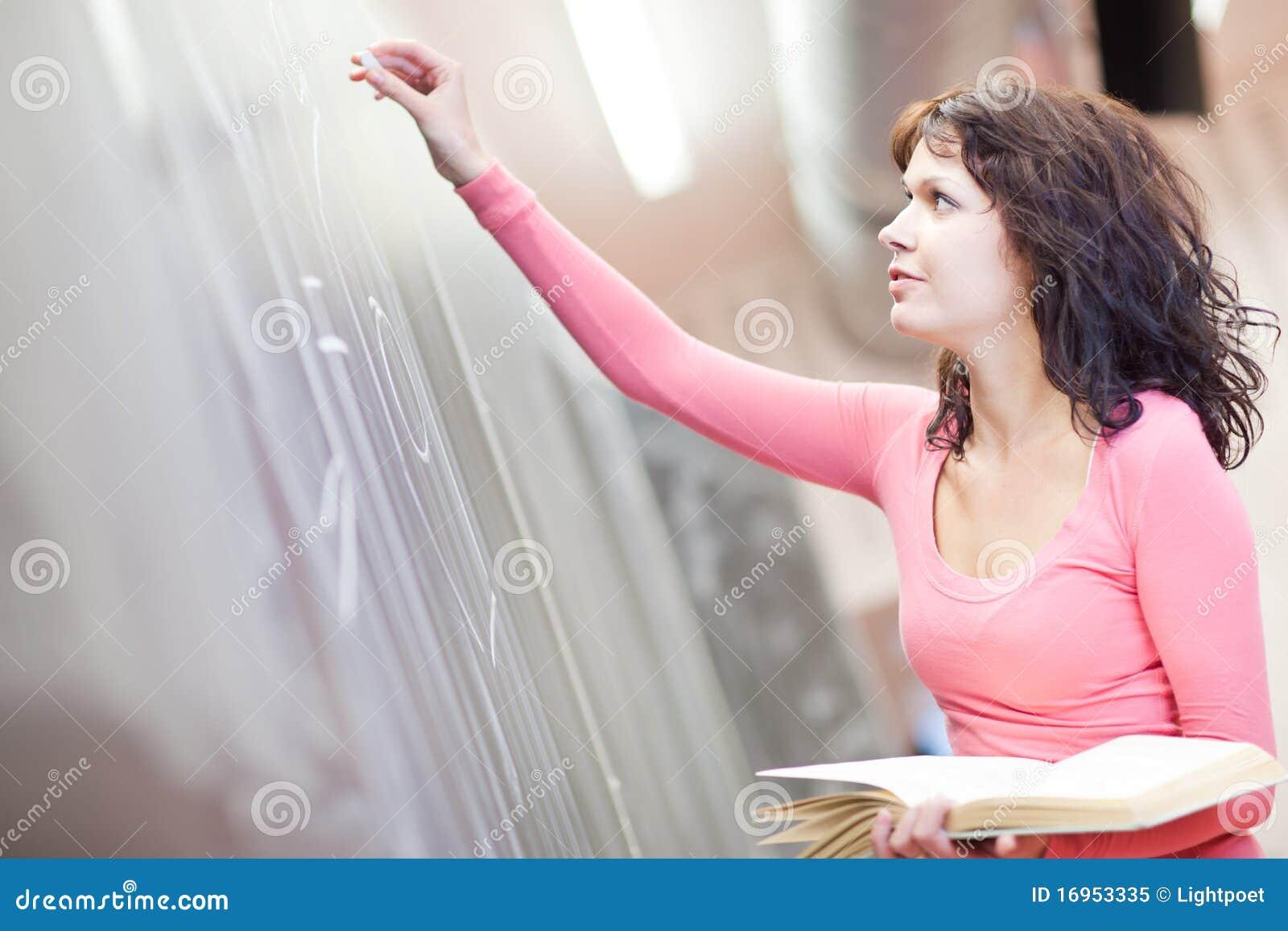 Escritura joven del estudiante universitario en la pizarra
