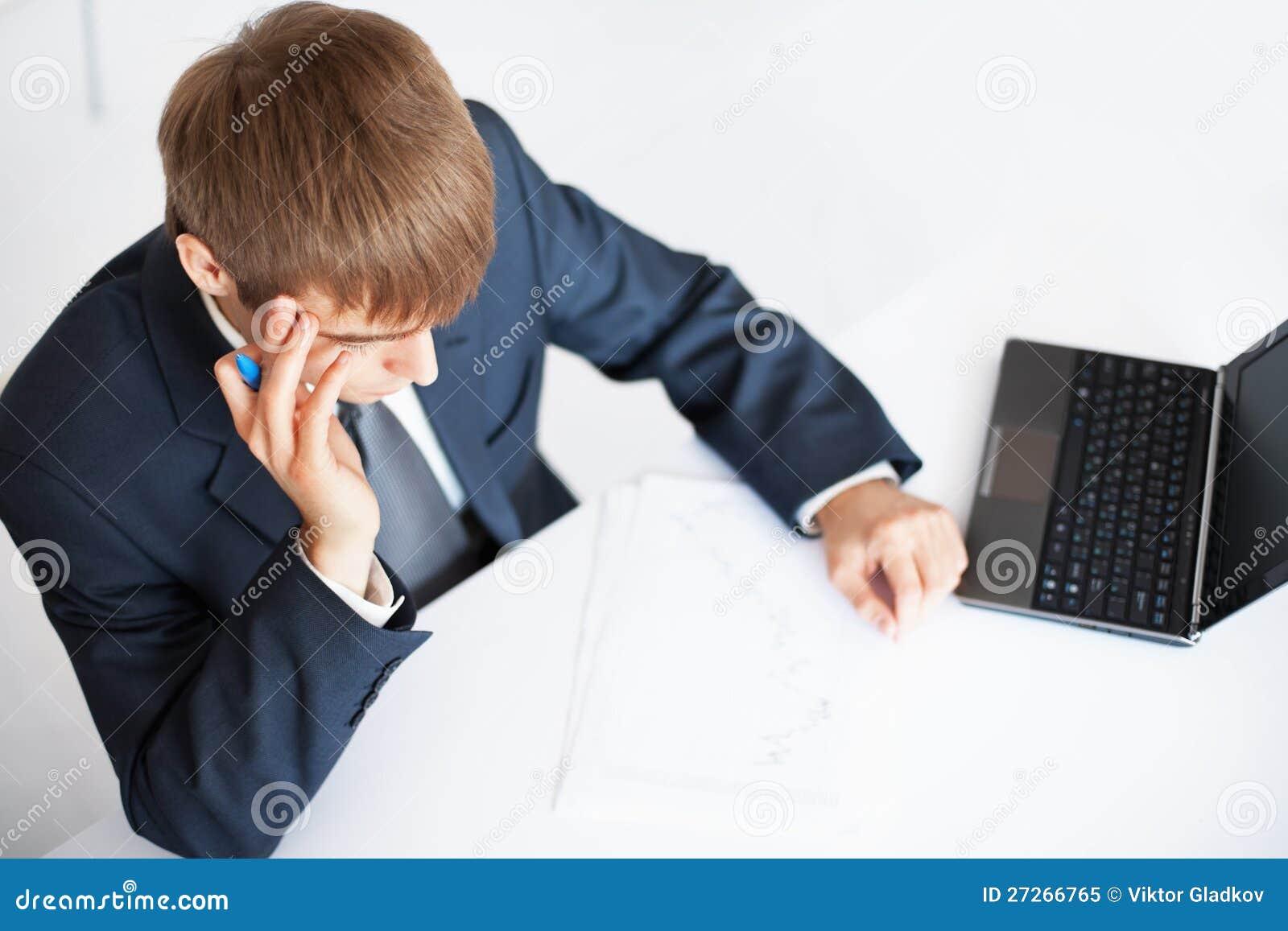Escritura joven del hombre de negocios en papeleo