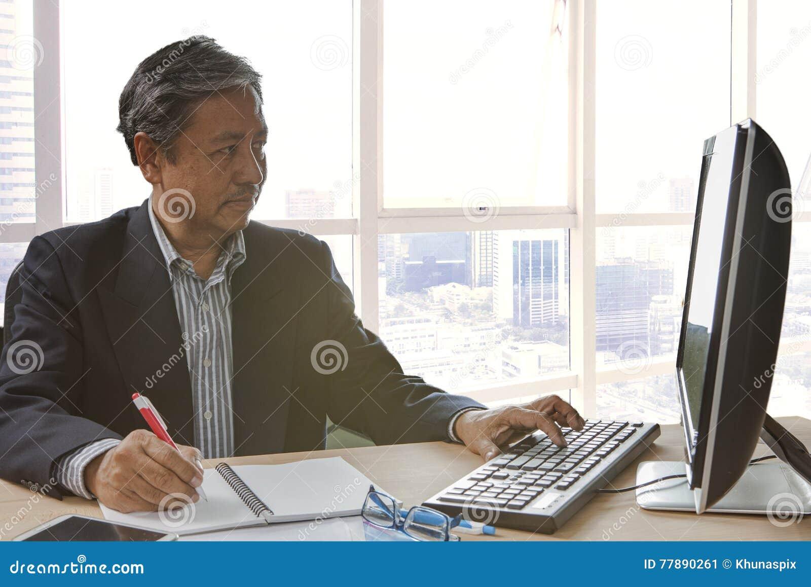 Escritura Y Funcionamiento Mayores Del Hombre De Negocios Del Asain En Computor De La PC Foto de archivo