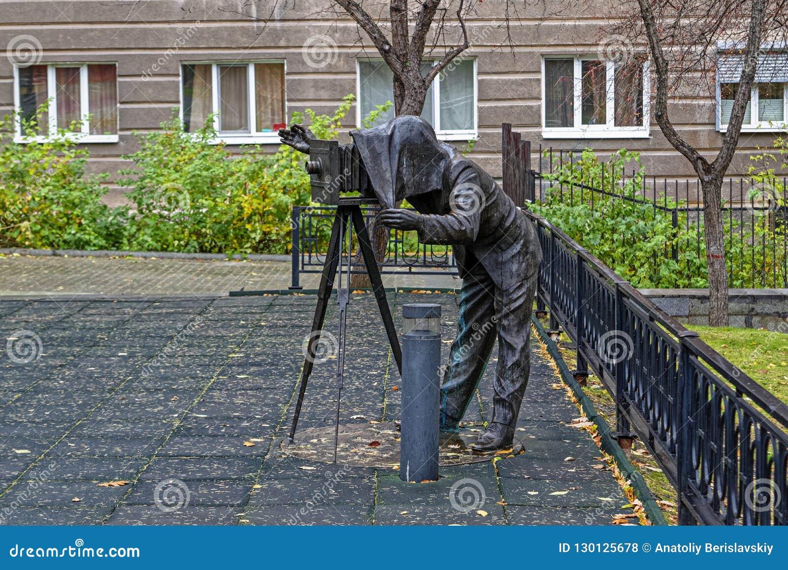 Escultura de bronce de un fotógrafo con una cámara del vintage en el parque