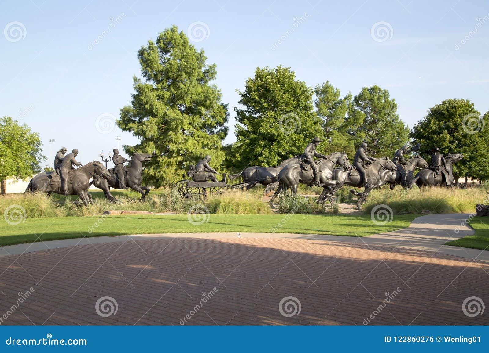 A escultura de bronze do grupo agradável na terra centenária corre o monumento