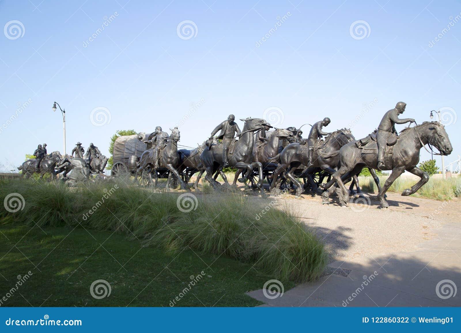 A escultura de bronze na terra centenária corre o monumento Oklahoma