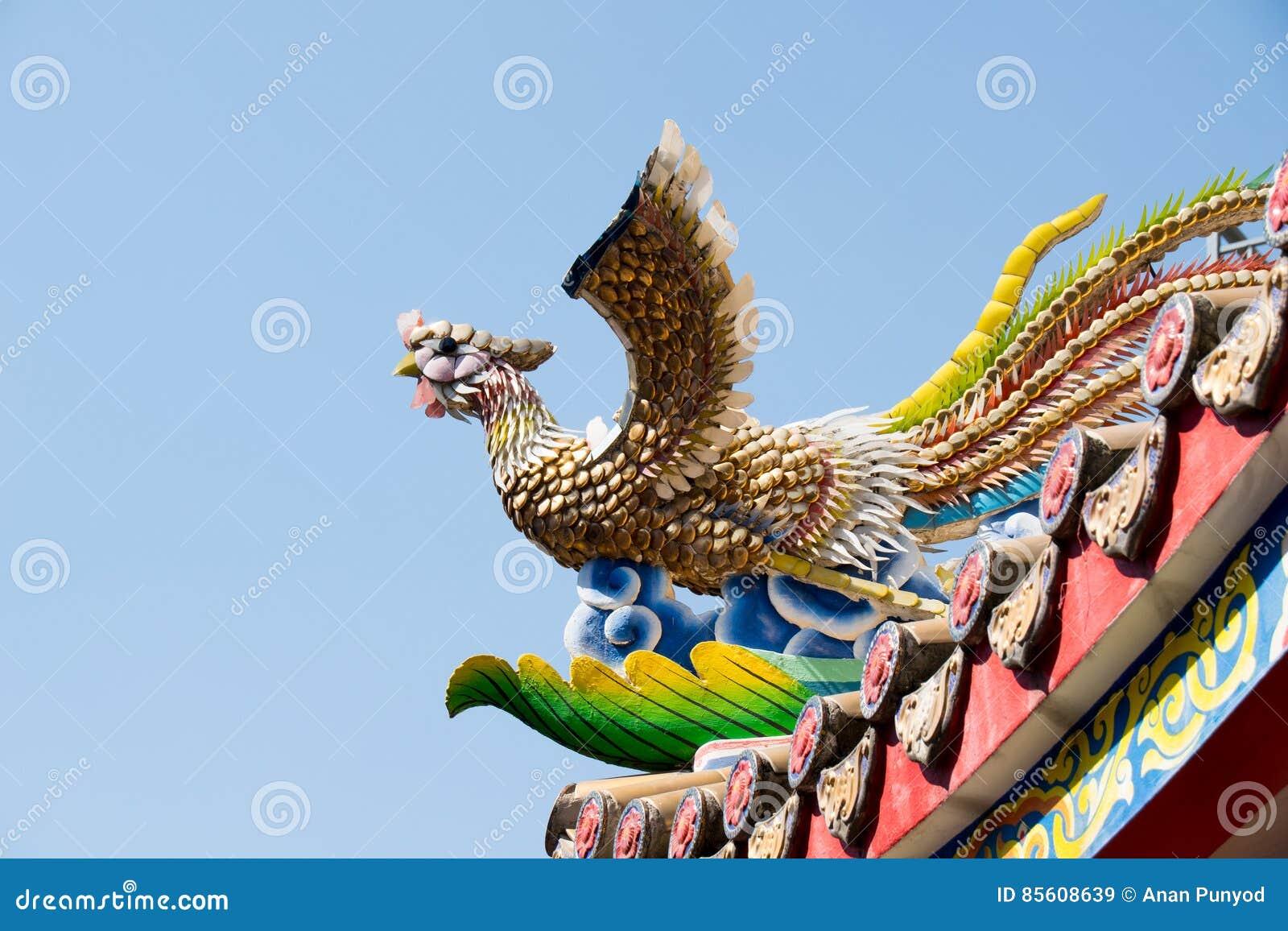 Escultura de cerámica del pájaro del chino tradicional en capilla del tejado
