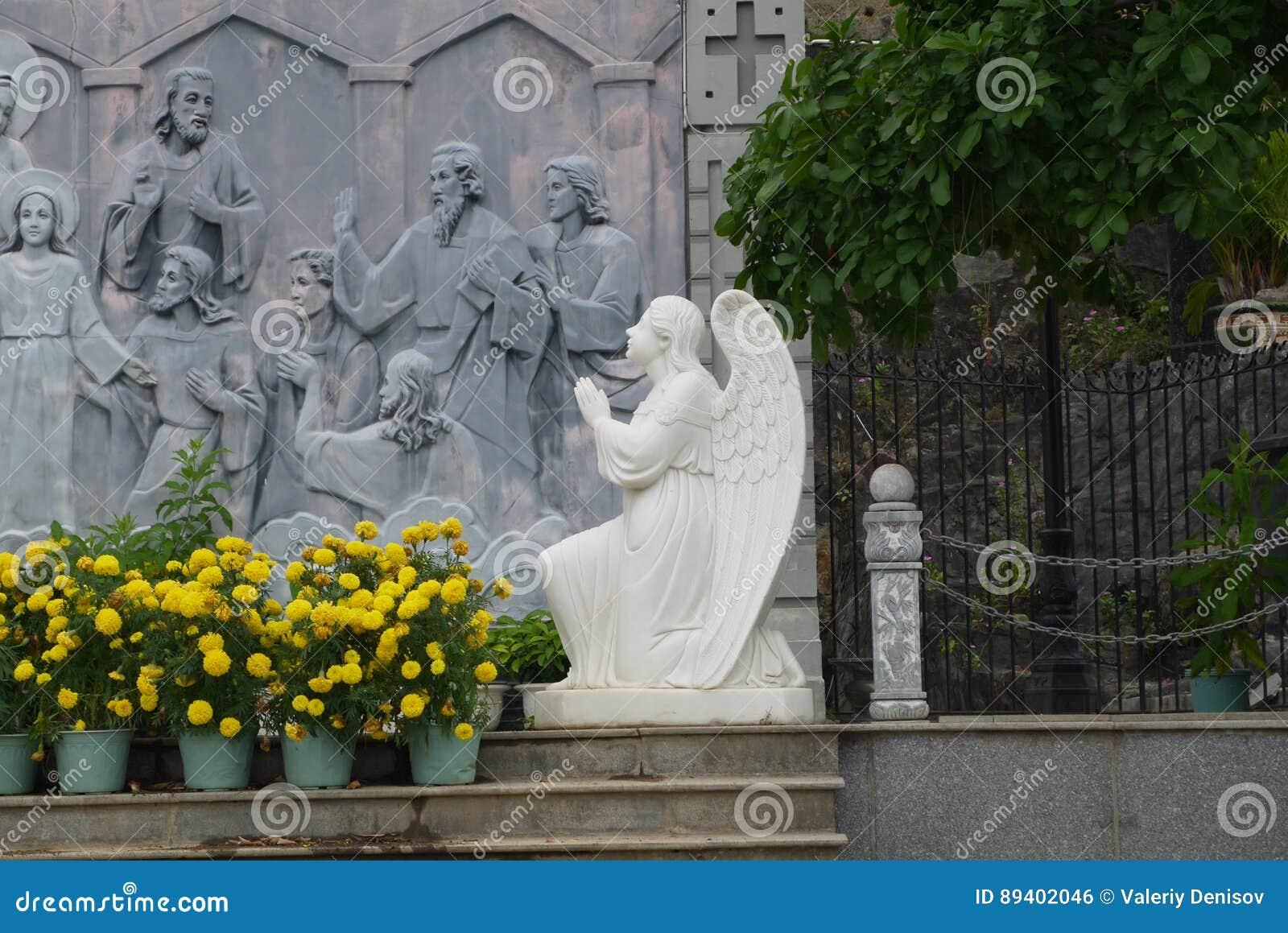 Escultura de um anjo do ajoelhamento em uma parede com lotes em um tema bíblico